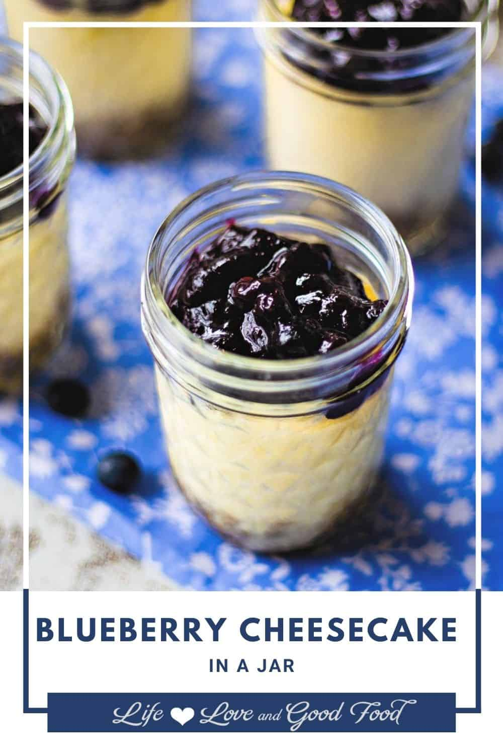 Blueberry Cheesecake in a Jar with a graham cracker crust, creamy baked cheesecake filling, and a delicious blueberry compote topping is the ultimate Summer time—or anytime—dessert! Devout cheesecake fans will flip over these smooth and velvety individual cheesecakes. The filling is straight-out classic cheesecake—not the no-bake stuff—baked in a water bath for a delicate and rich texture. The blueberry topping is a mixture of fresh blueberries and blueberry jam melted together.