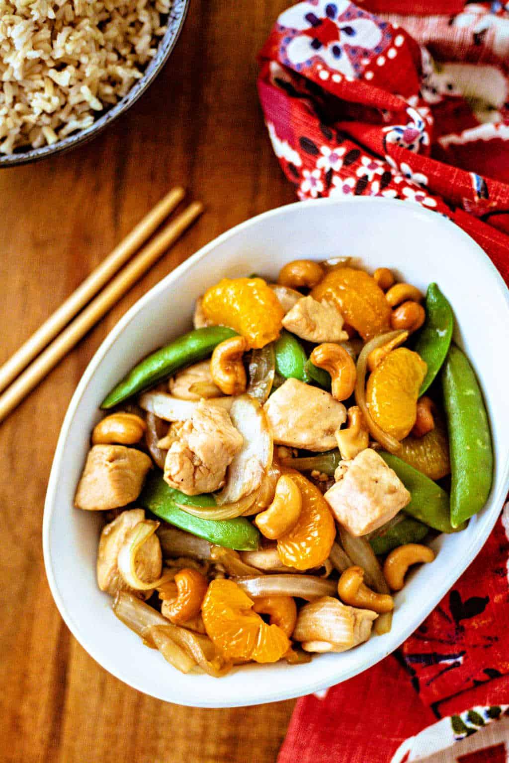 Easy Orange Cashew Chicken in a white bowl with chopsticks