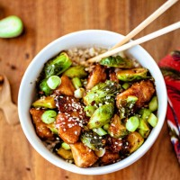 Sriracha Chicken and Brussels Sprouts Stir Fry in a white bowl with chopsticks