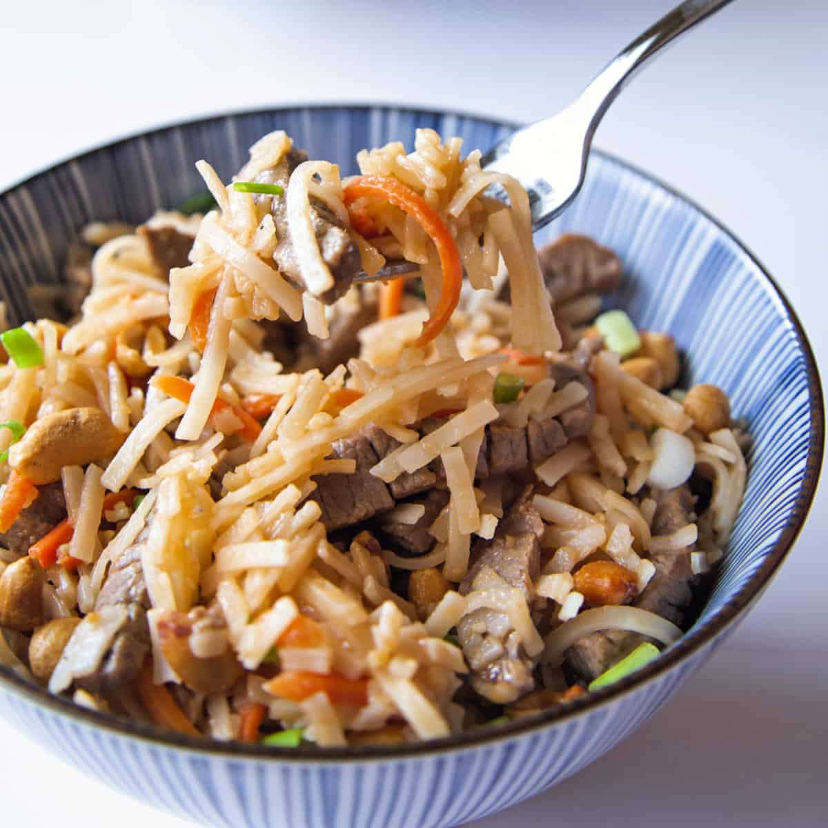 beef pad thai in a blue striped bowl with a fork