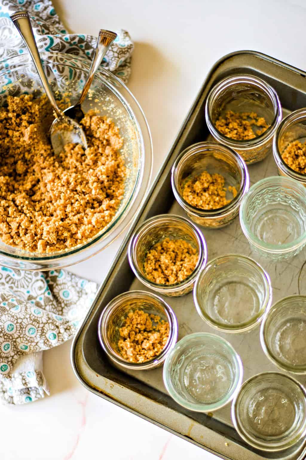 spooning graham cracker crust mixture into mason jars