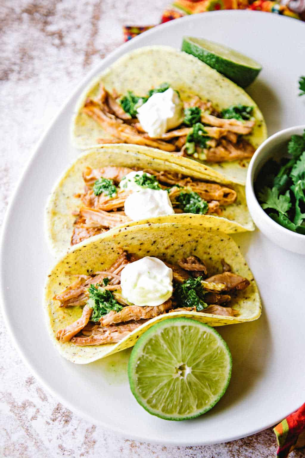 pork carnitas on a white platter with lime slices