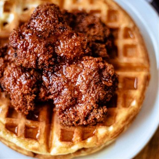 chicken and waffles with honey sriracha on a white plate