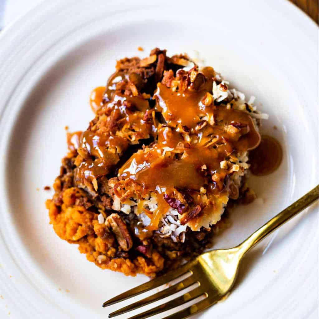 german chocolate pumpkin dump cake on a white plate with a gold fork
