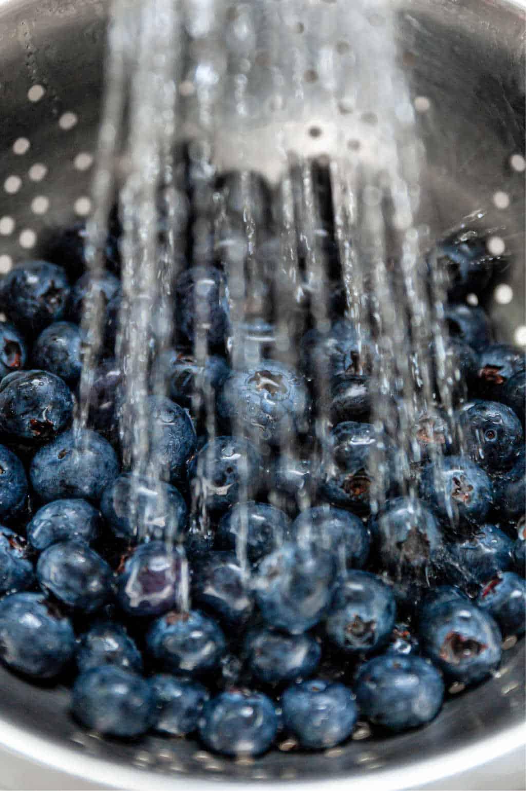blueberries in colander under running water