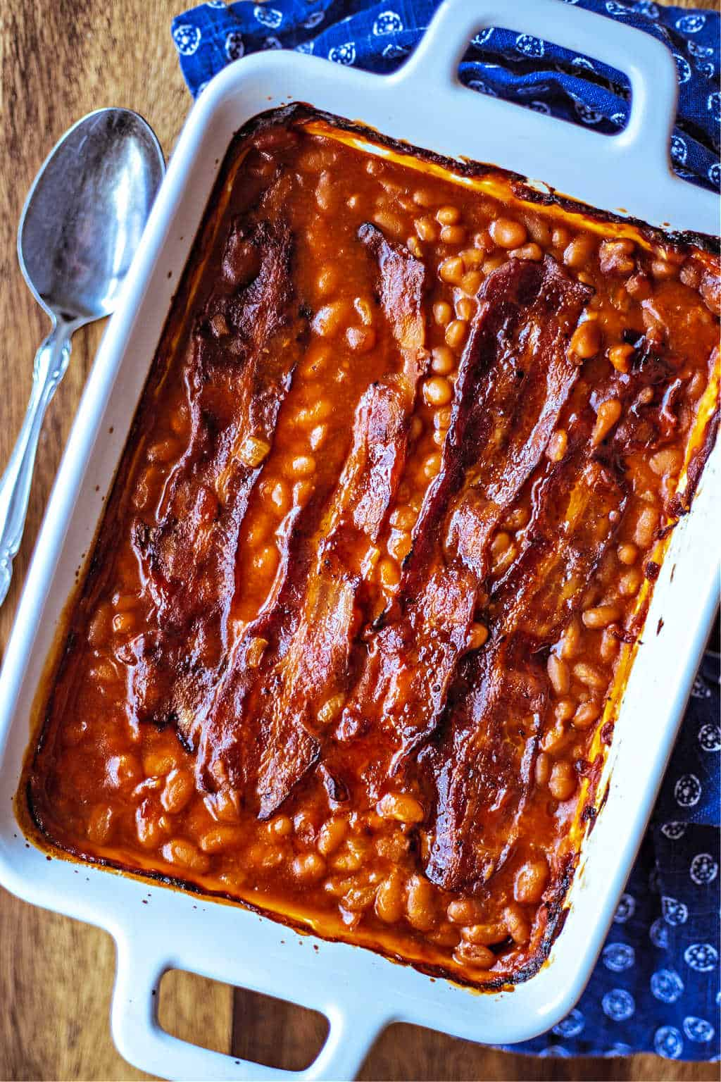 a baking dish of baked beans and bacon on a wooden table