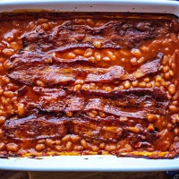 Easy Baked Beans with strips of bacon in a white baking dish