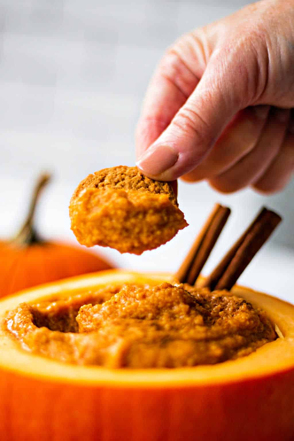 dipping a ginger snap into pumpkin mascarpone dip