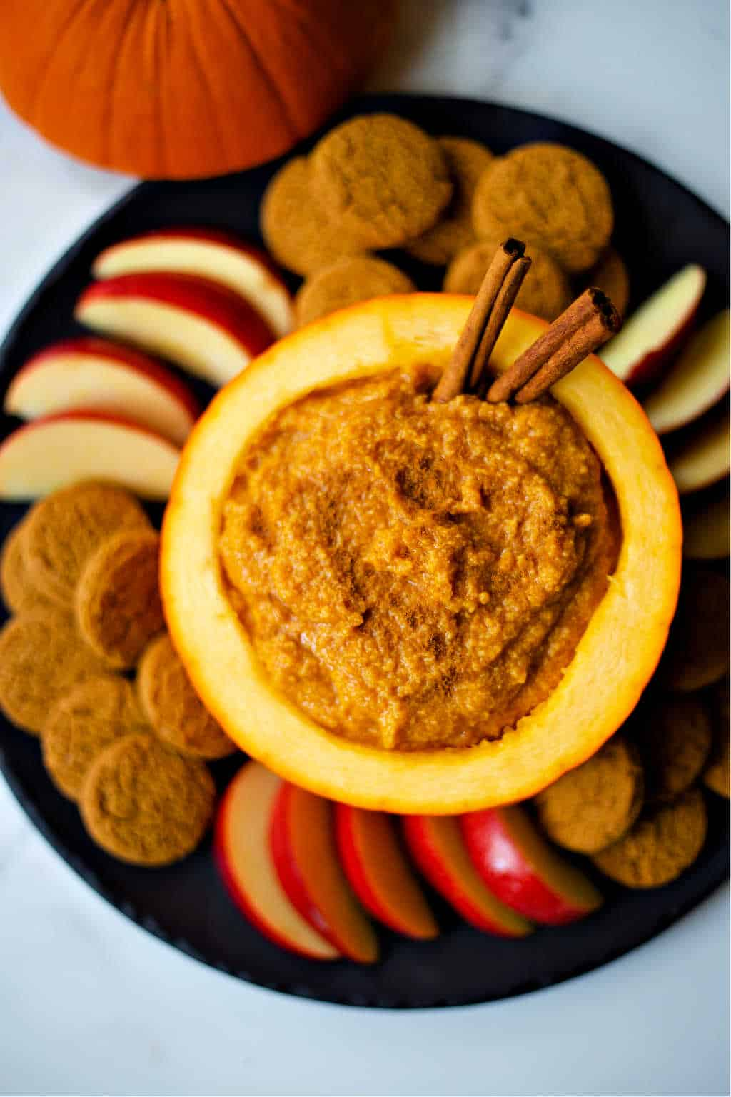 Pumpkin Mascarpone Dip on a black platter with ginger snaps and apple slices