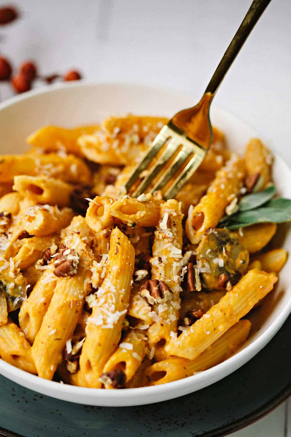 penne pasta with pumpkin pasta sauce in a white bowl with a fork