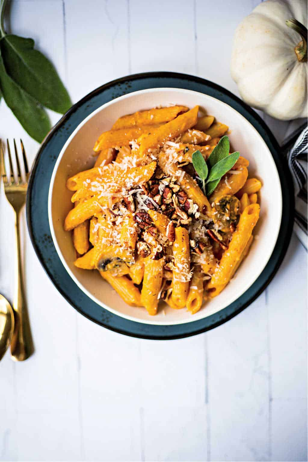 penne pasta with pumpkin pasta sauce in a white bowl