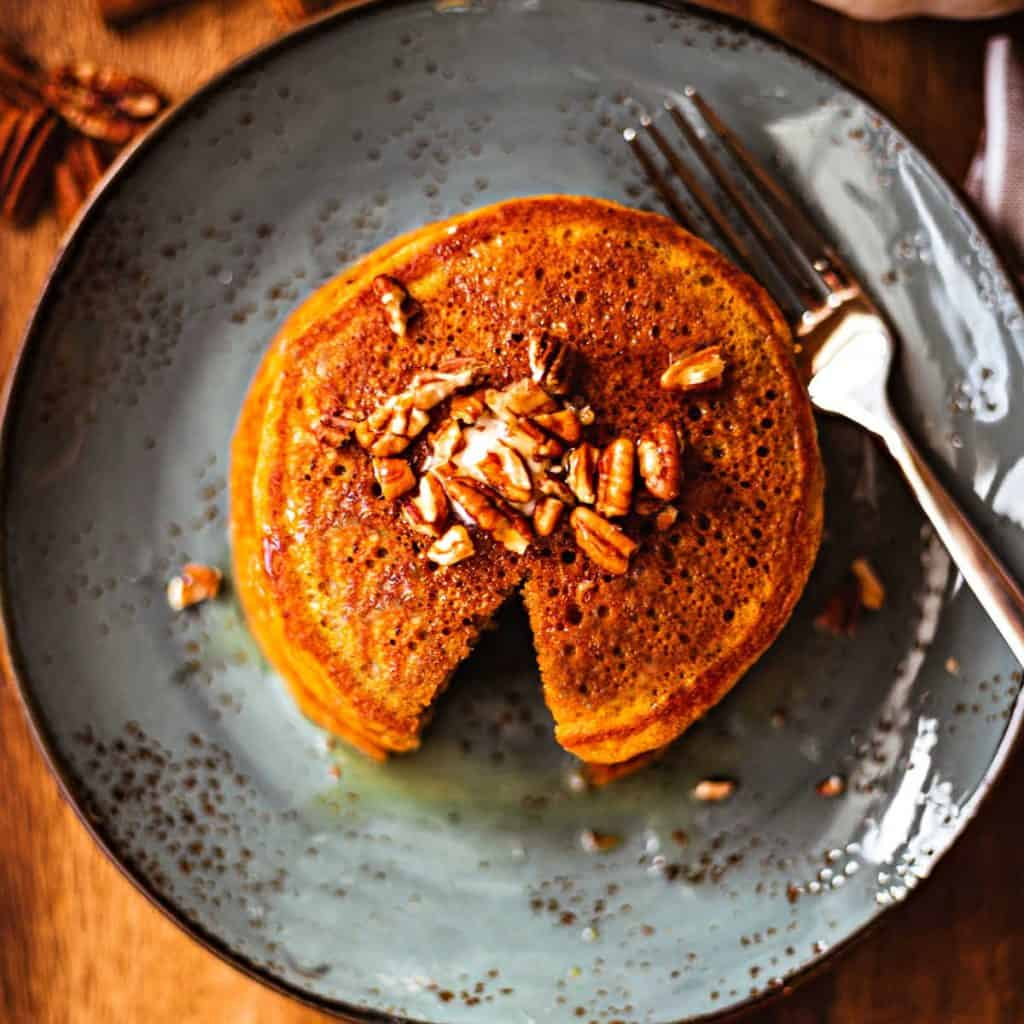 Pumpkin Spice Pancakes with maple syrup and toasted pecans on a blue plate with a fork
