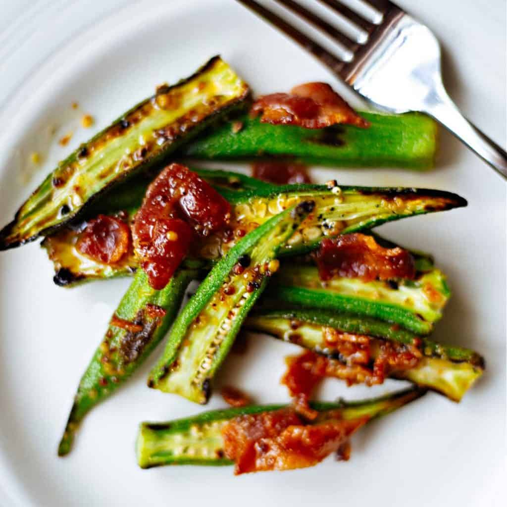 roasted okra with warm bacon vinaigrette on a white plate with a fork