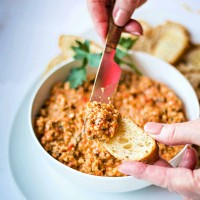 spreading roasted red pepper tapenade on a baguette