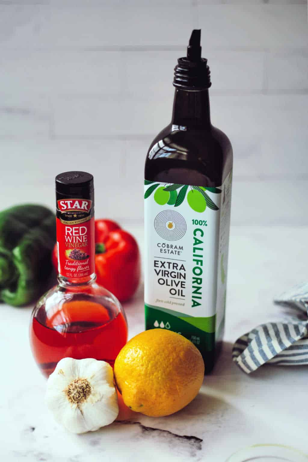 a bottle of red wine vinegar and olive oil with garlic and lemon