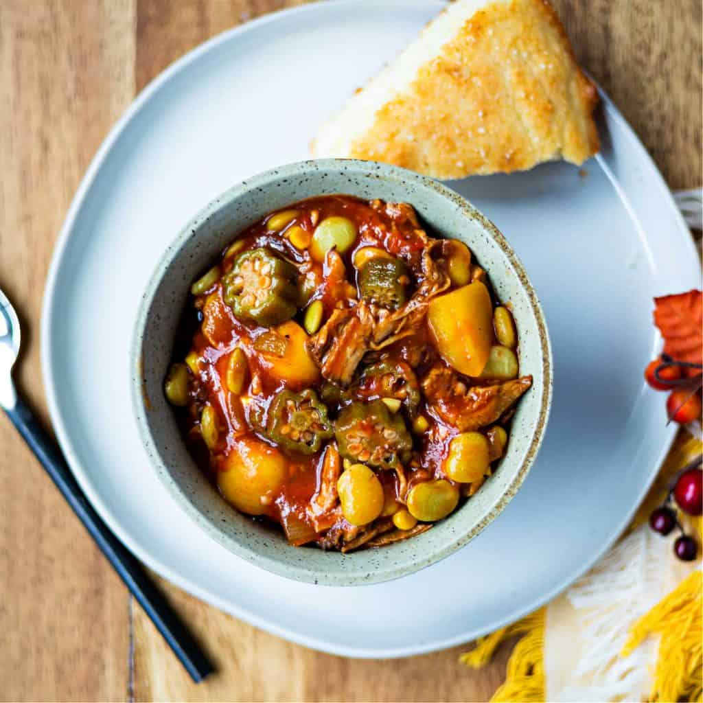 Easy Brunswick Stew in a bowl on a plate with a piece of cornbread
