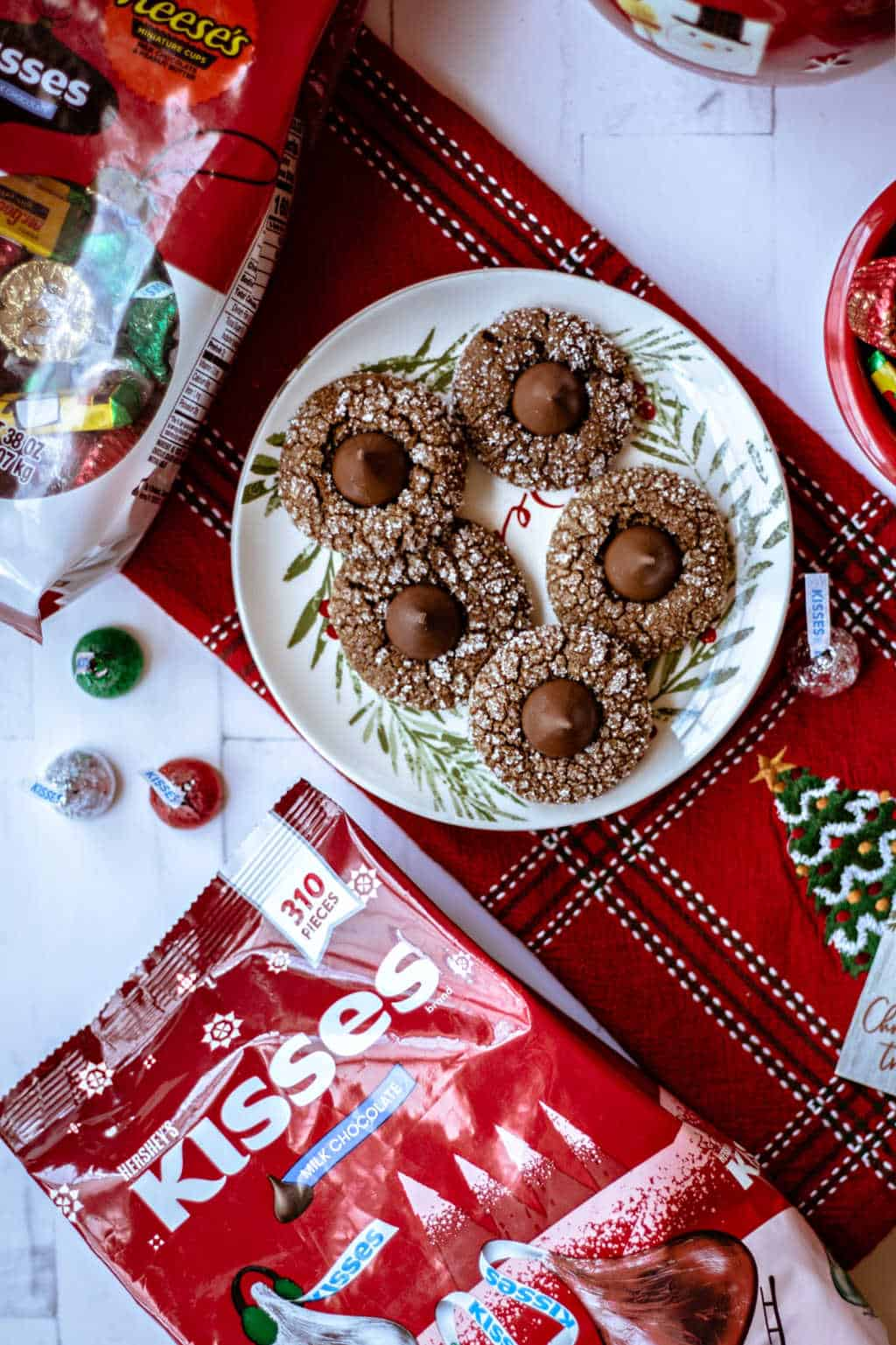 A plate of Gingerbread Kiss Cookies on a red dish towel with candy on a table
