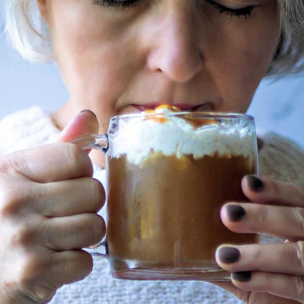 a woman sipping a cup of hot apple cider with whipped cream