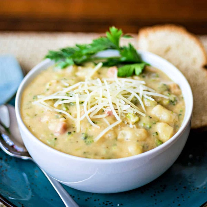 Italian Potato Broccoli Cheese Soup in a white bowl on a blue plate