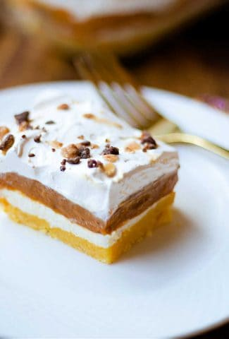 a slice of pumpkin delight on a plate on a wooden table