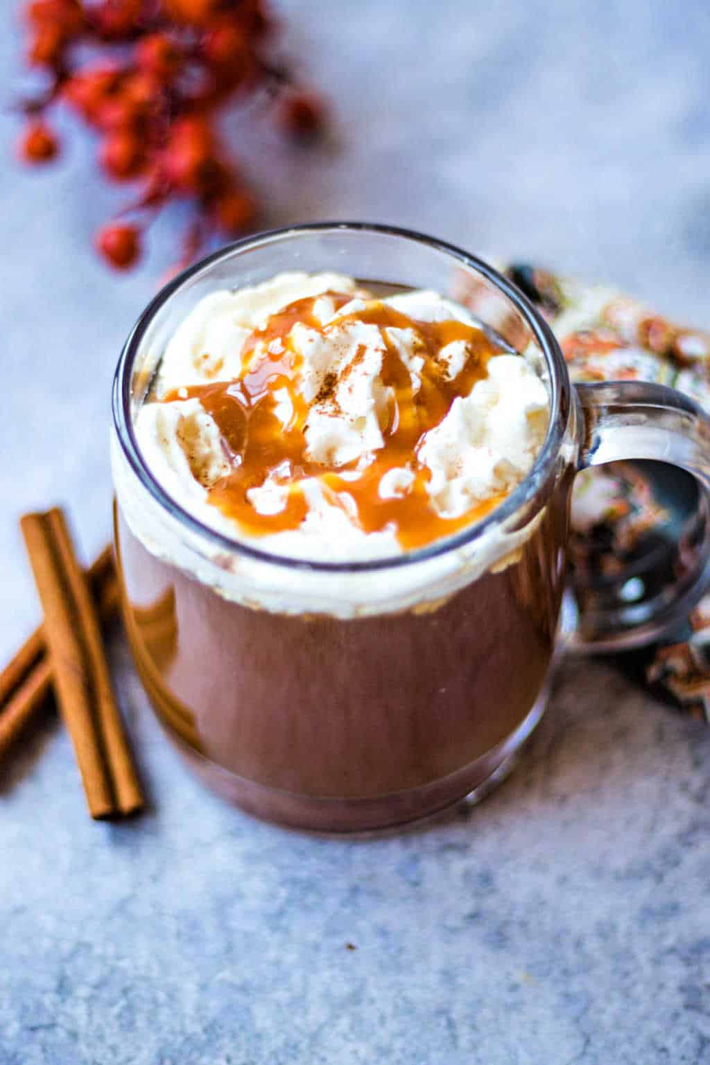 hot apple cider in a glass mug with whipped cream
