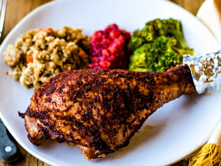 a roasted turkey leg on a white plate with sides on a wooden table