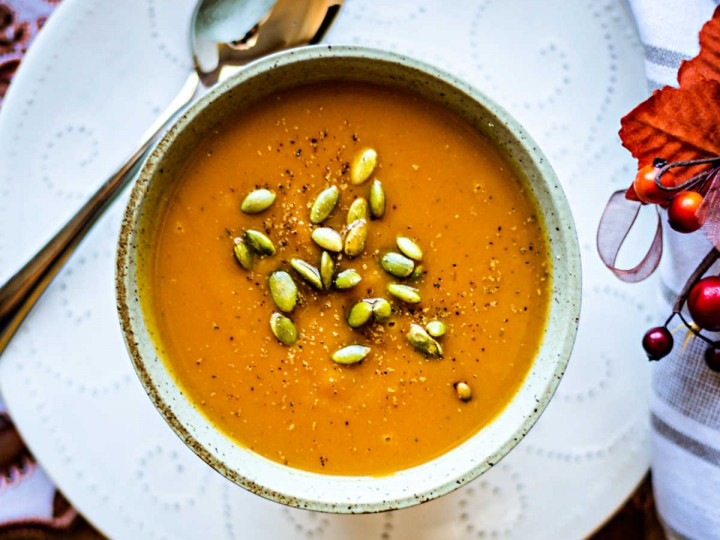 a bowl of butternut squash soup on a white plate
