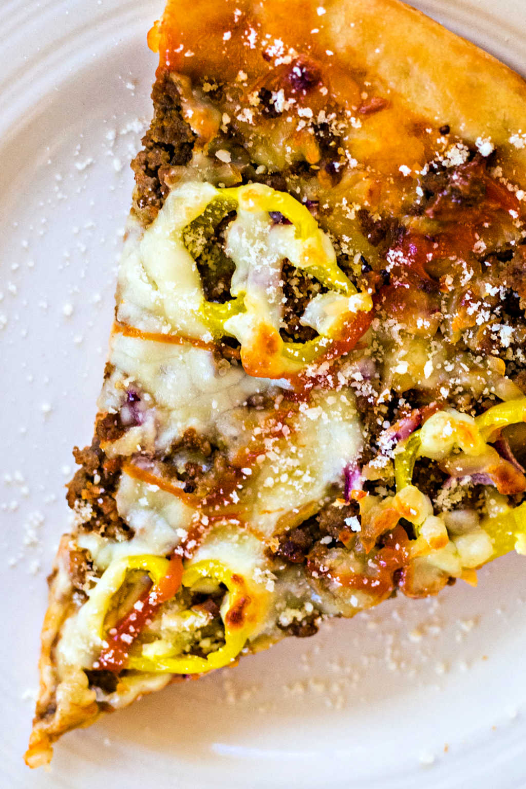 close up of a slice of cheeseburger pizza