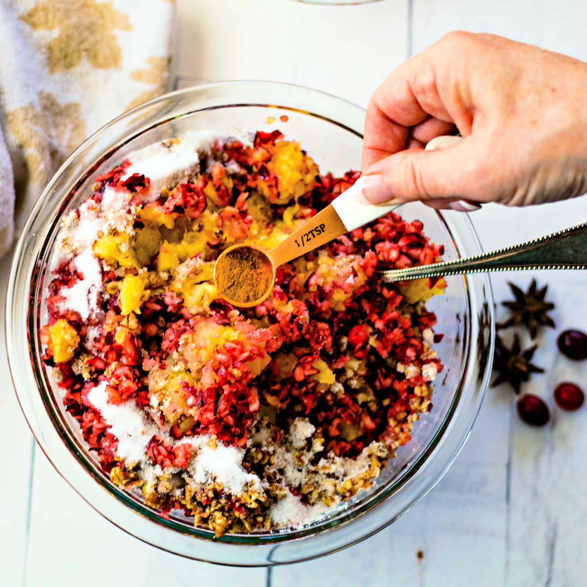 adding cinnamon to a bowl of chopped cranberries for relish
