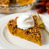 a slice of sweet potato pie with a dollop of whipped cream on a white plate