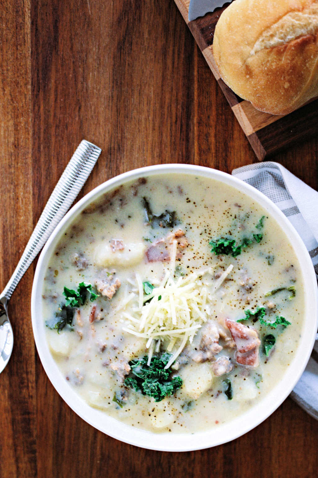 a bowl of zuppa toscana soup on a wooden table