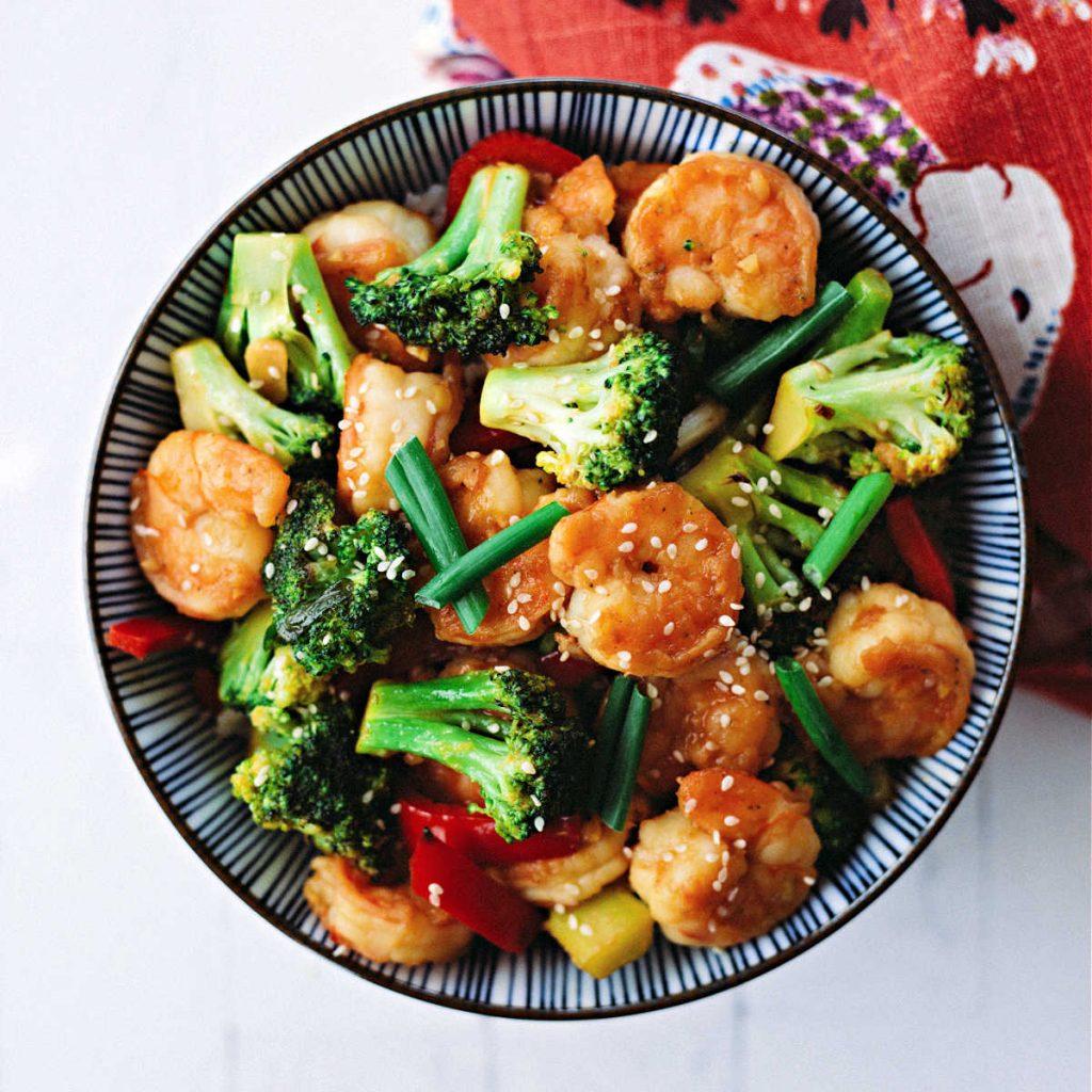 shrimp broccoli stir fry in a bowl on a table