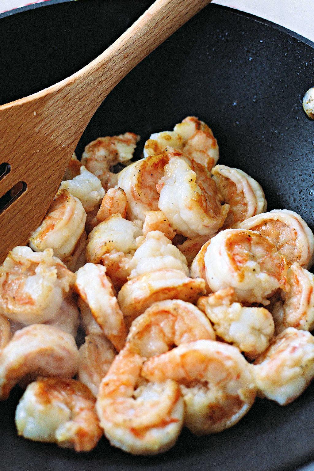 stir frying shrimp in a wok