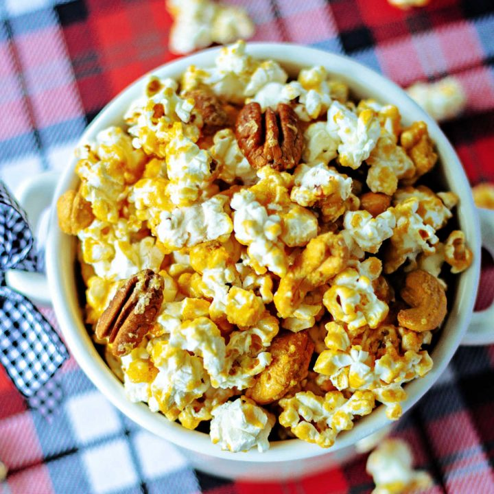 Nutty Caramel Corn in a white bowl on a Christmas plaid tablecloth