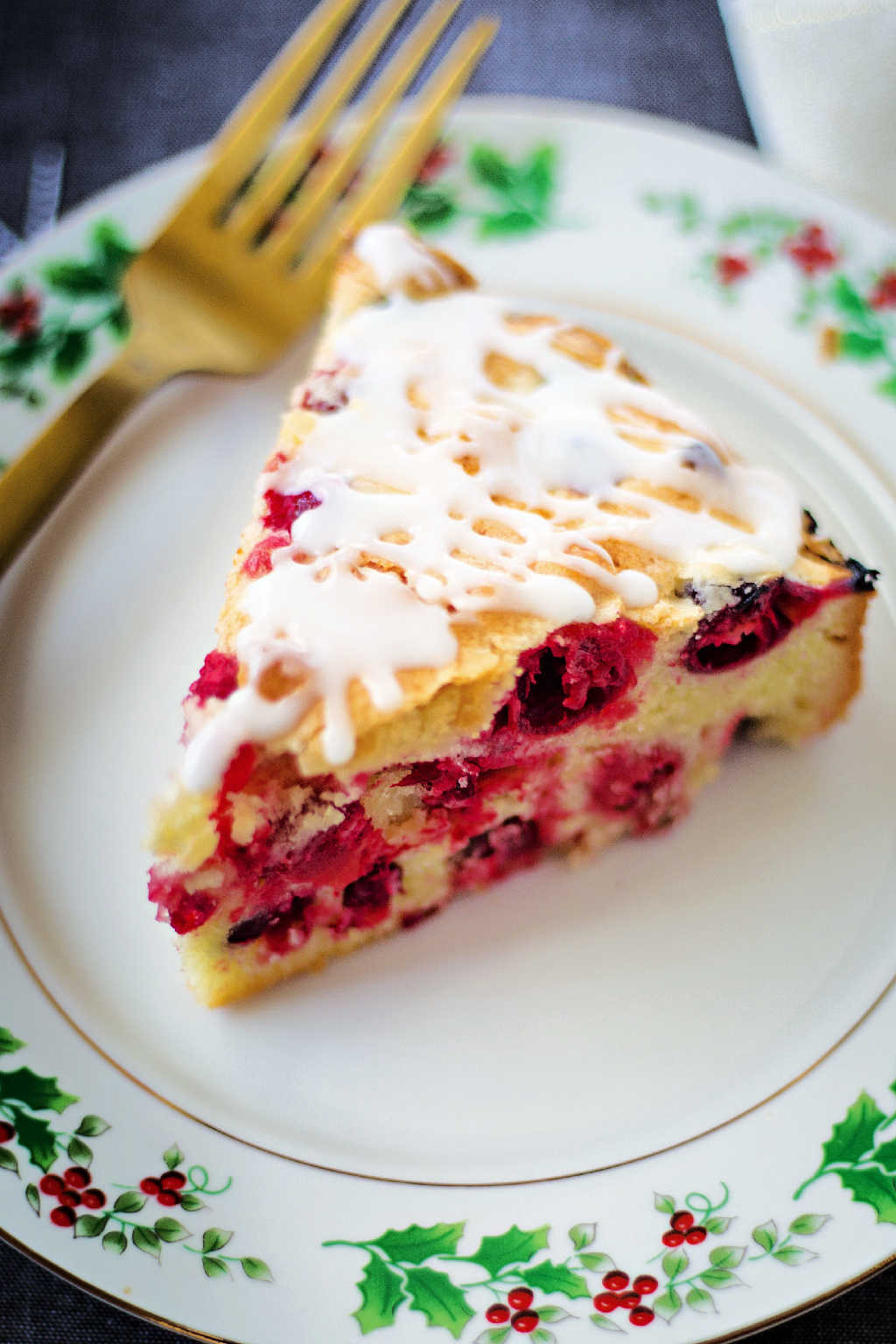 a slice of cranberry cake on Christmas china plate