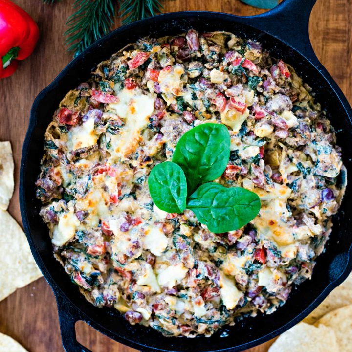 Sausage, Bean, and Spinach Dip in a cast iron skillet on a wooden table