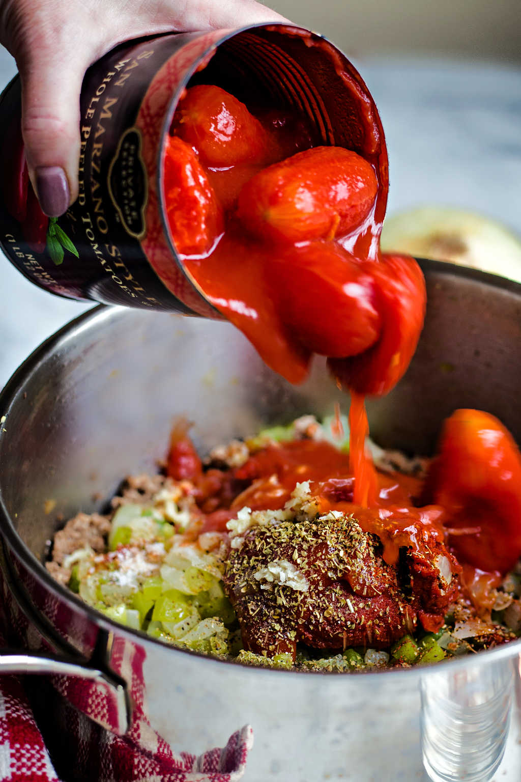 Adding a can of whole tomatoes to a pot of spaghetti sauce.