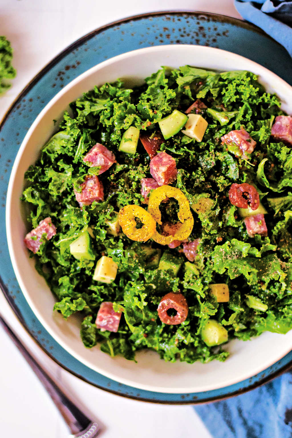 chopped kale salad in a white bowl on a blue plate