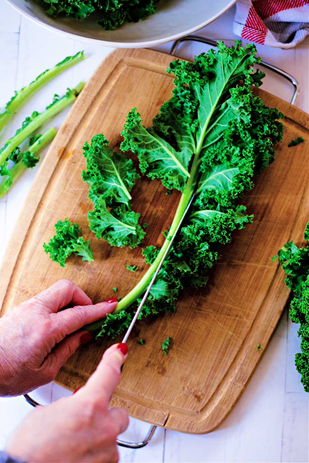 cutting kale leaves away from the stem on a cutting board
