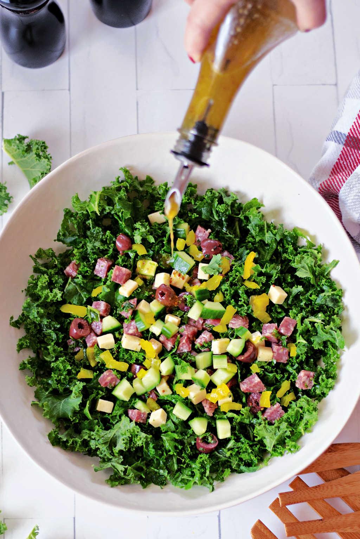 pouring vinaigrette onto a kale salad in a white bowl