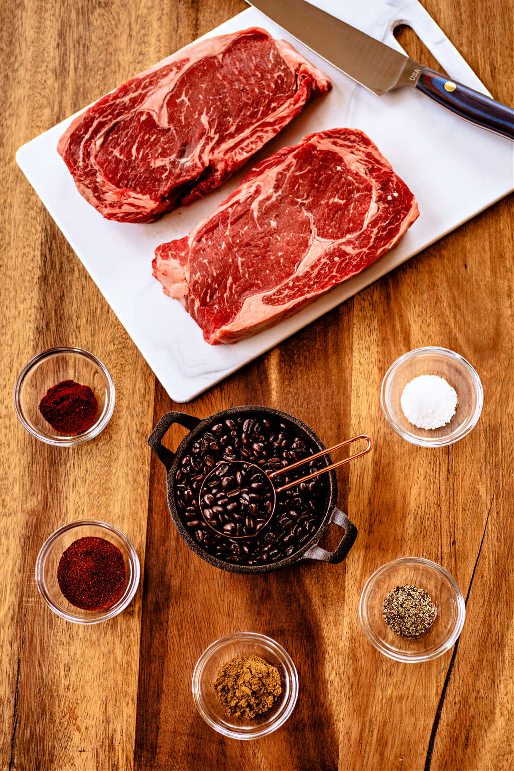 spices and dark roast coffee beans on a wooden table with 2 ribeye steaks, prepping for dry rub