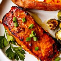Grilled salmon on a white plate with a baked sweet potato