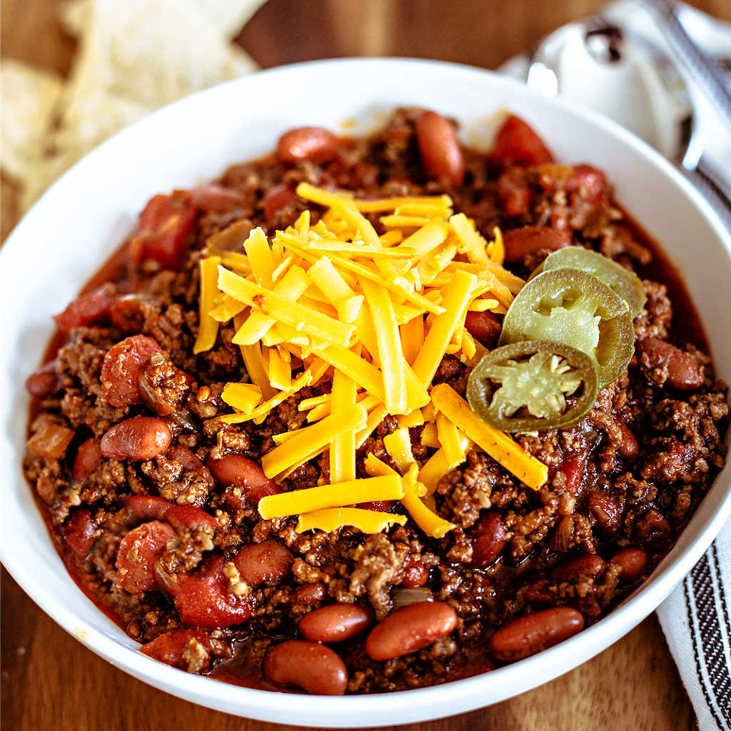 ground beef chili in a white bowl topped with cheese and jalapeno slices