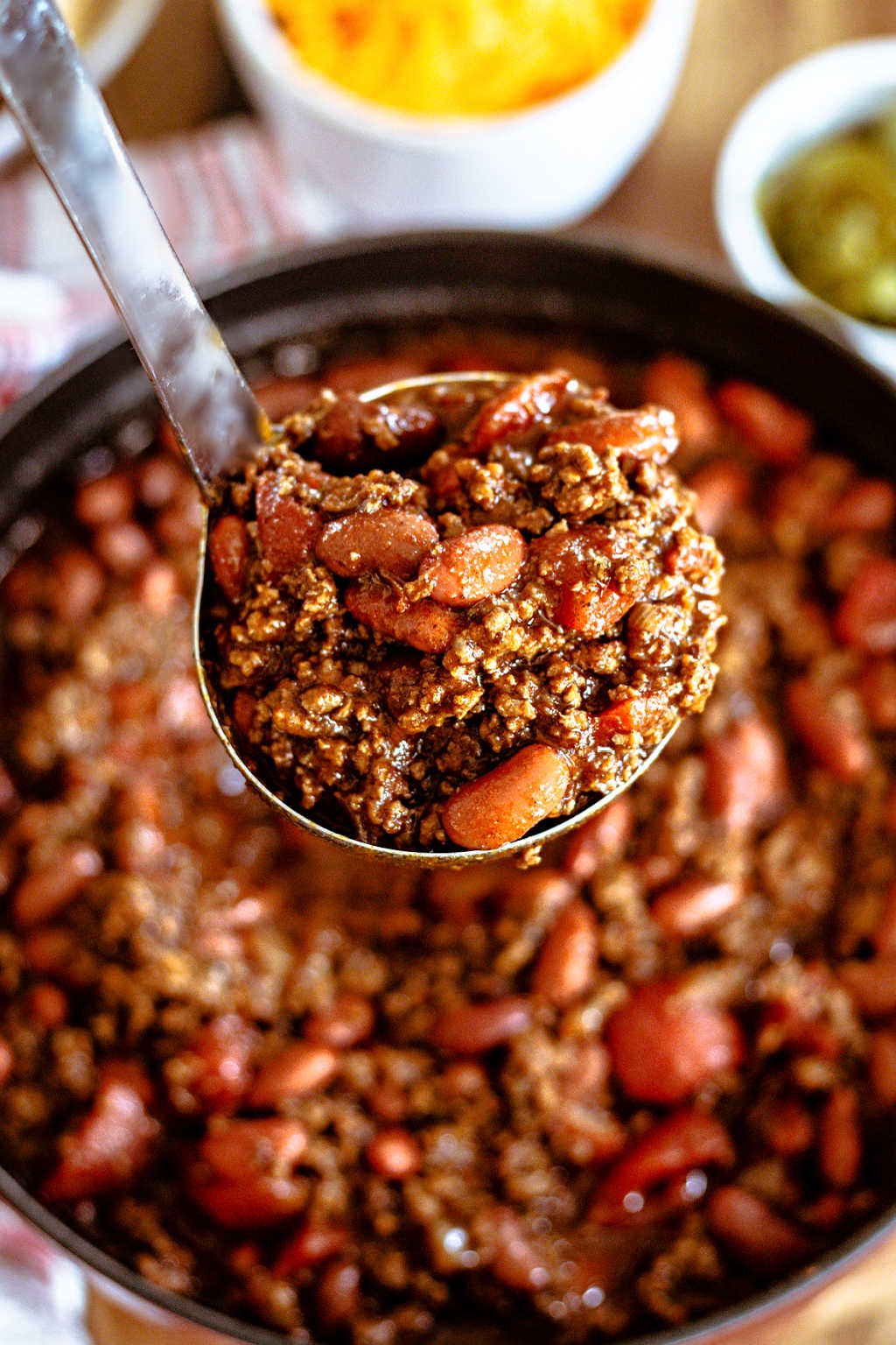 a ladle full of ground beef chili lifted out of a pot