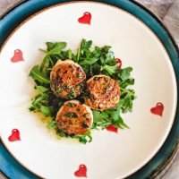 pan-seared scallops on a bed of arugula on a white plate