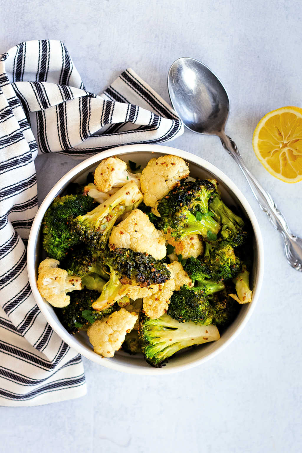 roasted broccoli and cauliflower in a white bowl on a table
