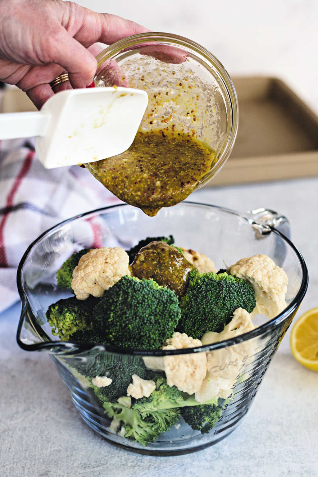 pouring mustard sauce on broccoli and cauliflower in a mixing bowl