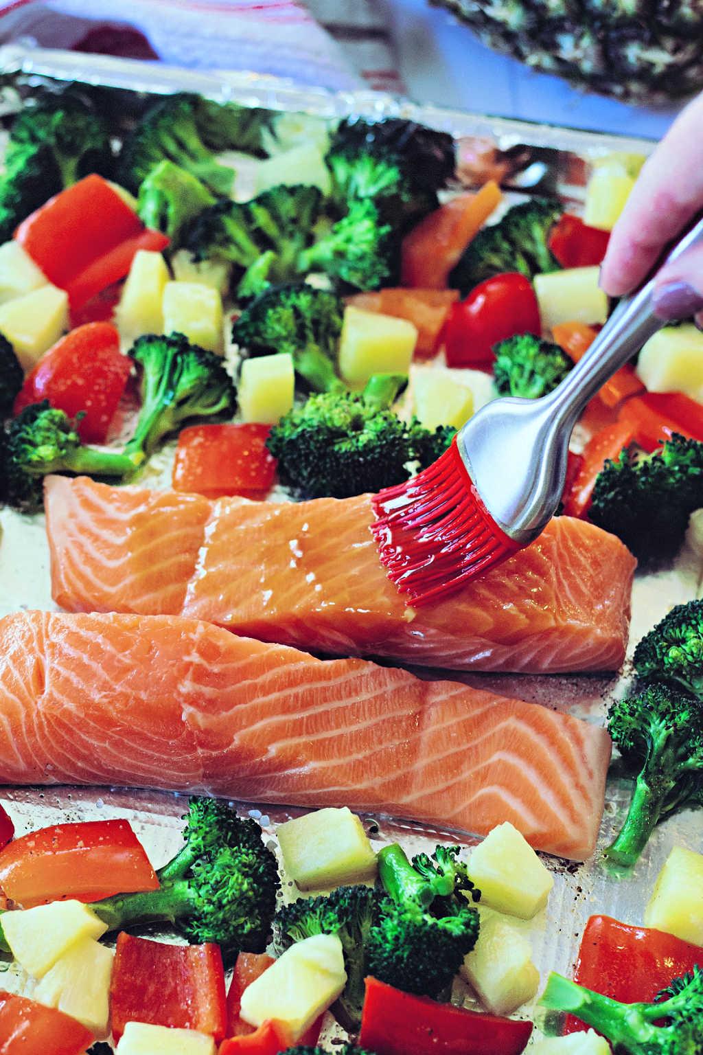 basting teriyaki sauce on salmon to bake