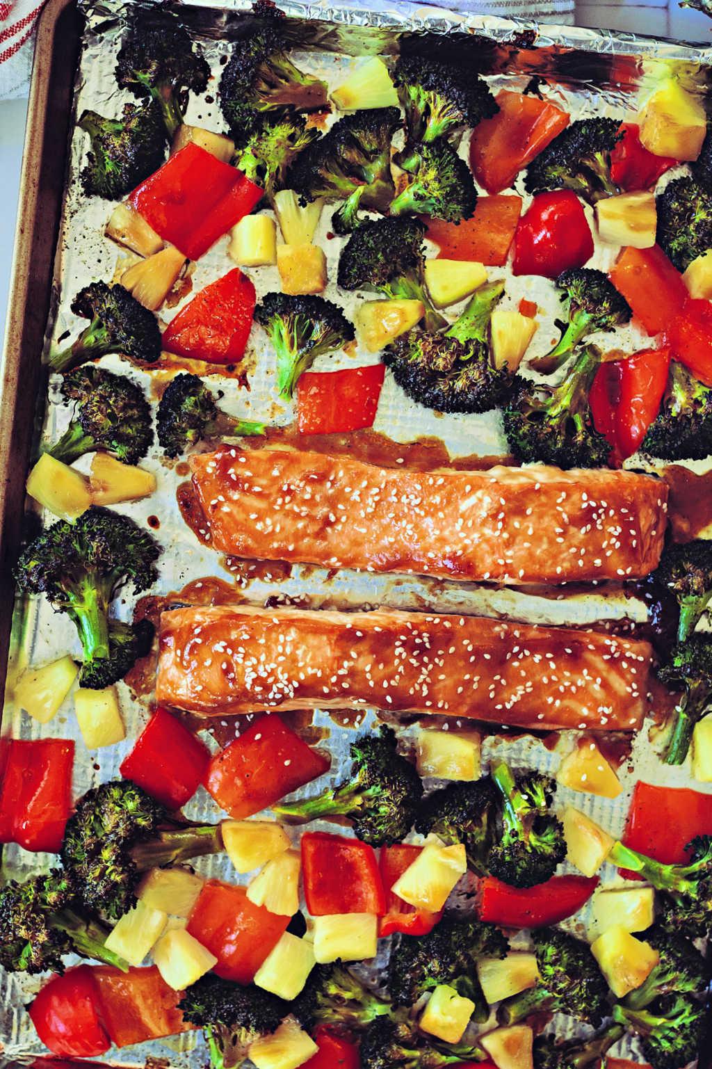 teriyaki salmon, broccoli, red bell pepper, and pineapple on a sheet pan