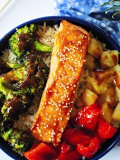 teriyaki salmon in a bowl with brown rice, roasted broccoli, red bell pepper, and pineapple